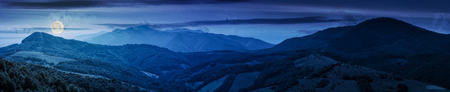 panorama of beautiful mountain ridge at night in full moon light. perfect countryside landscape. rural field on the nearest forested hills. Mighty Borzhava ridge in the distance Stock Photo