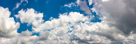 amazing cloud formations on a dark blue sky. beautiful side lit cloudscape panorama in summer Stock Photo