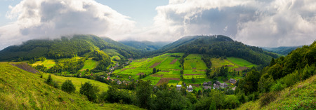 panorama of a rural area in mountains. gorgeous forenoon with beautiful clouds on the sky. agricultural fields on hills calm and peaceful life concept. Stock Photo