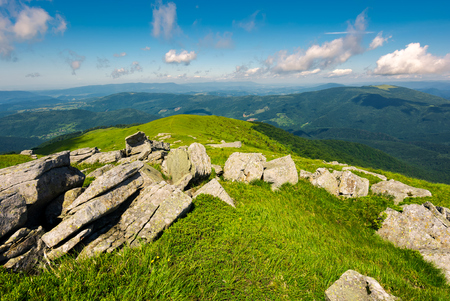 boulders down the grassy slope of a hill. beautiful sky over the distant mountains. stunning summer weather Stock Photo
