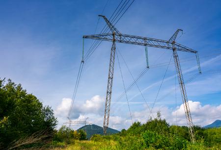 Stromleitungsturm auf einem Hügel. Riesige Metallkonstruktion in wunderschöner Landschaft. Kraft und Energiekonzept