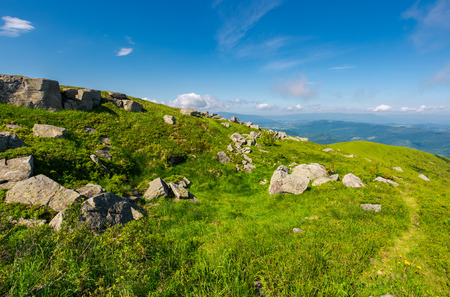 grassy meadow on hillside. huge rocky formation. beautiful summer scenery in wonderful weather. Stock Photo