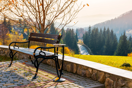 bench on a hill in beautiful autumn countryside. lovely mountainous landscape with road through forest