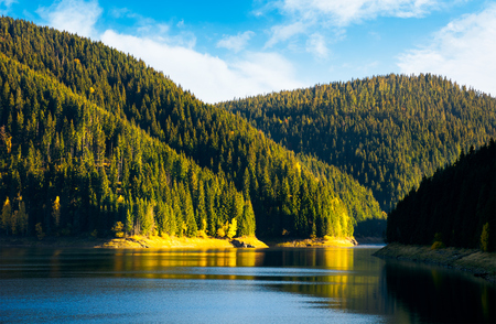 storage reservoir in mountain at sunrise. beautiful  landscape in early autumn Stock Photo