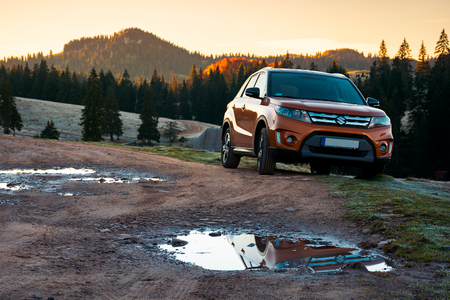 Apuseni, Romania - OCT 15, 2017: orange Suzuki Vitara SUV on a country road in mountains at sunrise. beautiful autumn landscape with spruce forest.travel Europe by car concept