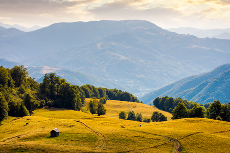 hut on the grassy hill at sunset. beautiful mountain ridge in the distance. wonderful summer landscape Stock Photo
