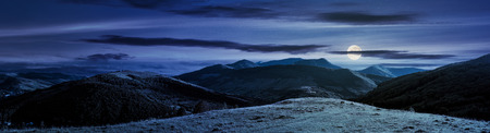 panorama of mountainous countryside at night in full moon light. beautiful evening weather with cloudy sky over the ridge