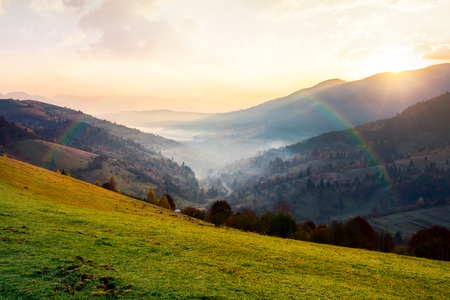 rainbow above the village in foggy valley. beautiful mountainous countryside at sunrise in autumn