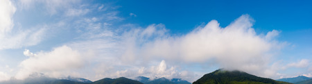 wonderful dynamic cloudscape above the mountain ridge. beautiful panoramic nature background Stock Photo