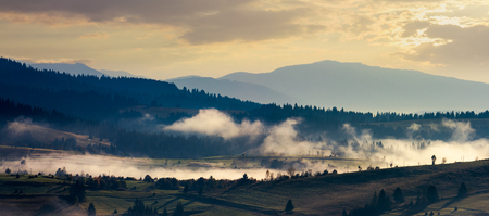 panorama of countryside in the morning. beautiful landscape in mountains with fog rising above the valley and hill