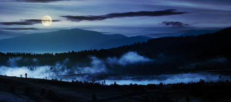 panorama of countryside at night in full moon light. beautiful landscape in mountains with fog rising above the valley and hill Stock Photo