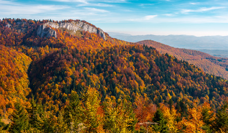 gorgeous mountainous autumn landscape. cliff above the forest with colorful foliage. beautiful view in evening light with blue sky Stock Photo