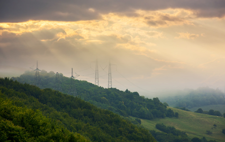 foggy autumn countryside in mountains. power line tower on the forested hill touch the cloud. beautiful golden light Stock Photo