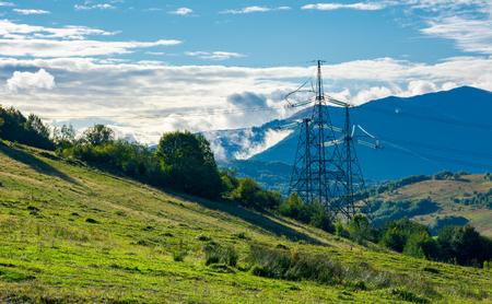 power line tower on the hill. huge mountain in clouds in the distance. autumn countryside Stock Photo