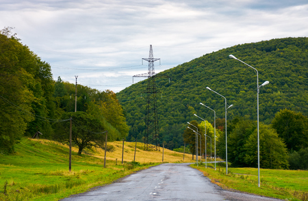 country road in mountains. lights and power line tower along the road Stock Photo