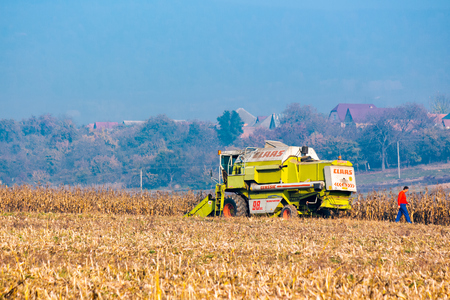 Shyroke, Ukraine - NOV 11, 2015: broken combine harvester in the corn field near the village. combine operator went searching for help. hot autumn afternoon