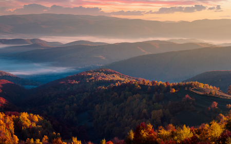 gorgeous red sunrise in mountains. forested hills in colorful fall foliage. fog in the distant valley Stock Photo