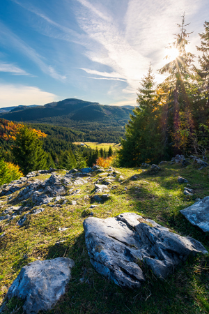 rocky cliff above the forested valley. beautiful autumn sunrise in mountainous landscape. Zdjęcie Seryjne