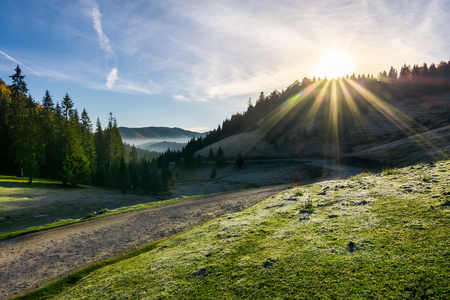 beautiful foggy landscape in autumn. winding road leads to distant valley full of fog. sun rise above the mountain. hoar on the grassy meadow Stock Photo