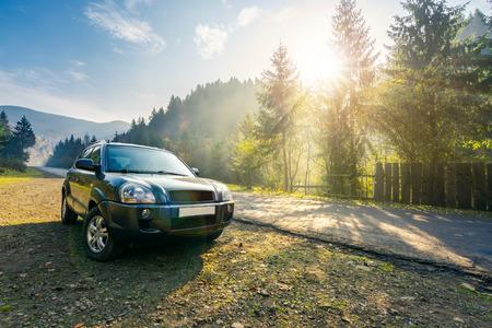 SUV en camino rural en montañas neblinosas. hermoso paisaje de transporte al amanecer en otoño. viajar en coche concepto