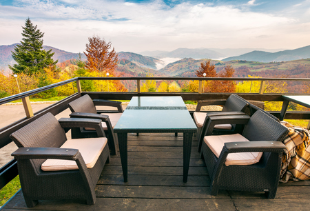 terrace with beautiful view in to the mountains. autumn season with red foliage on forested hills. cloud inversion in distant valley. wonderful vacation concept Stock Photo