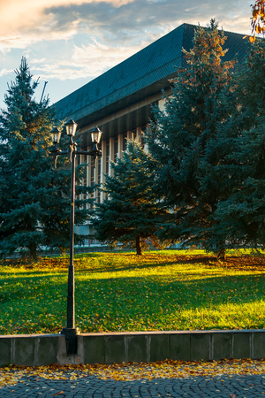 park lantern near the Uzhgorod Drama Theater. lovely urban scenery at sunrise in autumn Stock Photo