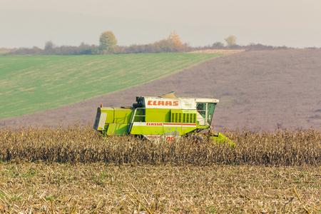 Shyroke, Ukraine - NOV 11, 2015:  harvester in the field removes the corn stalks in late fall haze day