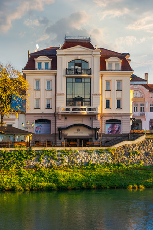 Uzhgorod, Ukraine - Nov 10, 2012: modern architecture of the old town on the bank of river Uzh at sunrise Stock Photo