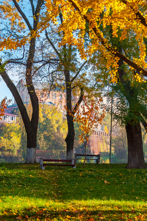 Uzhgorod, Ukraine - Nov 10, 2012: autumn park on Pravoslavna naberezhna in autumn foliage.  ancient building of University on the hill in the distance. beautiful sunny weather Stock Photo
