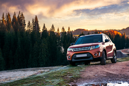 orange 4wd suv parked in mountain at sunrise. beautiful autumn scenery with gravel road through spruce forest. travel Europe by car concept Stockfoto