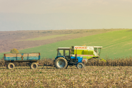 Shyroke, Ukraine - NOV 11, 2015: tractor and harvester in the field among the corn stalks in late fall  haze day Stock Photo