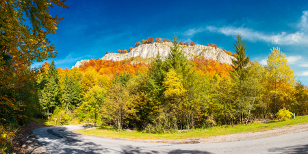 panorama of gorgeous serpentine in autumn forest. huge rocky formation on the hill above the path. beautiful nature and weather. colorful foliage Stock Photo