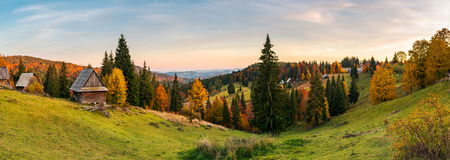 panorama of village in Apuseni mountains. beautiful autumn landscape at sunset. mixed forest in red foliage. wonderful rural countryside of Romania Stock Photo