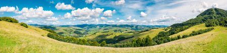 panorama of beautiful autumn countryside. forest behind the meadow. gorgeous cloudscape on the sky above the distant hills. wonderful warm and sunny september day for a walk or hike