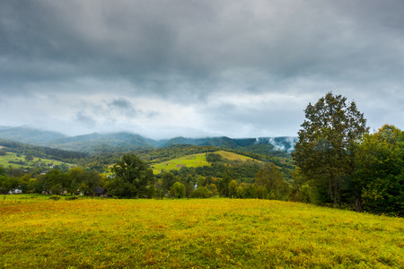grassy rural meadow in mountains. rainy september weather. distant ridge in clouds and haze Stock Photo