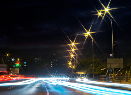 traces of car lights on the evening street. starburst of city lights. wide road leads to living area in the distance. busy night life concept Stock Photo