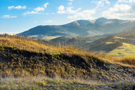 grassy hill in autumn mountains. lovely countryside. distant peak in snow on a bright sunny day Stock Photo