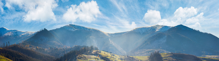 panoramic landscape of mountainous countryside in afternoon. gorgeous cloudscape above the ridge. grassy hills and naked trees. mountain tops in snow Stock Photo