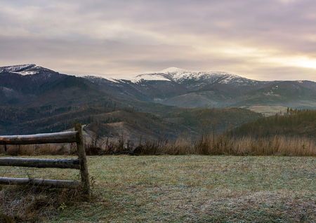 wooden fence on meadow with frozen grass. mysterious late autumn scenery with snow on tops of distant mountains Stock Photo - 108882724