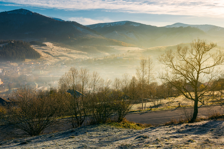 rural valley in autumn at sunrise. beautiful scenery in mountains. road down to village in haze and fog. distant mountain tops in snow Stock Photo - 108882737