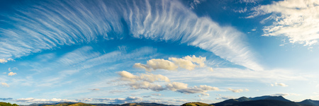panorama of a gorgeous cloudscape. dynamic high cloud formations on a windy autumn day in mountains Stock Photo