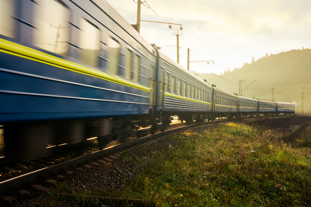 fast moving train through viaduct in mountains. old fashioned transportation concept. lovely countryside at sunrise Stock Photo - 108882876