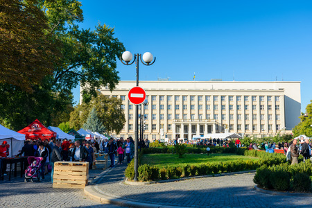 Uzhgorod, Ukraine - SEP 28, 2018: Czech days in TransCarpathia festival. 100 year celebration of Czechoslovakia declaration in 1918. Regional Administration building in the distance. people taste dishes, beer and listen to national music