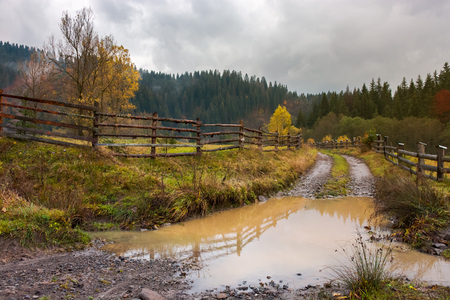 huge puddle on the country road. wooden fence along the path. deep autumn in mountainous countryside Stock Photo