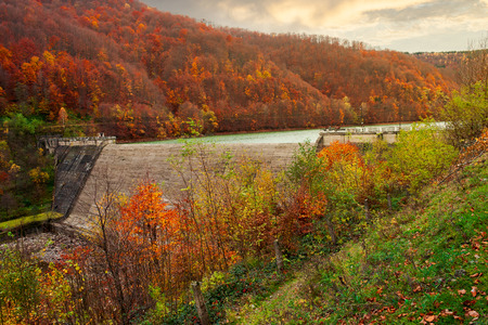 dam of water reservoir on the Tereblya river of Transcarpathia, Ukraine. beautiful autumn scenery with forest in red foliage