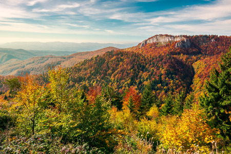 beautiful landscape in mountains of Romania. cliff above the forest in fall color. beautiful view in evening light with blue sky Stock Photo