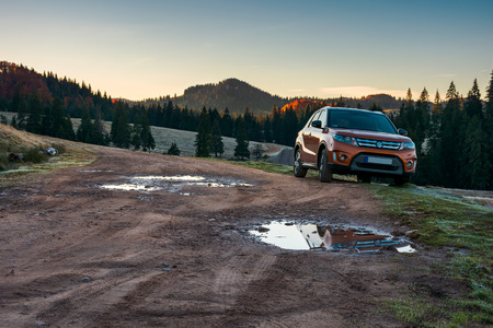 Apuseni, Romania - OCT 15, 2017: orange Suzuki Vitara SUV parked on the country road near forest in mountain at sunrise. beautiful autumn scenery. travel Europe by car concept Stock Photo - 109267188