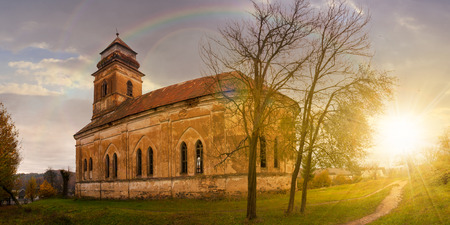rainbow above panorama of abandoned catholic church on hill at sunset