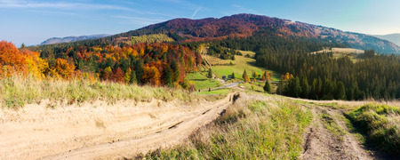 panorama of mountainous landscape in autumn. country road down the hill. parking lot in the valley. forest in fall colors Stock Photo