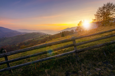 beautiful sunrise in mountains. countryside scenery in autumn. fence along the rural fields. distant mountains in haze